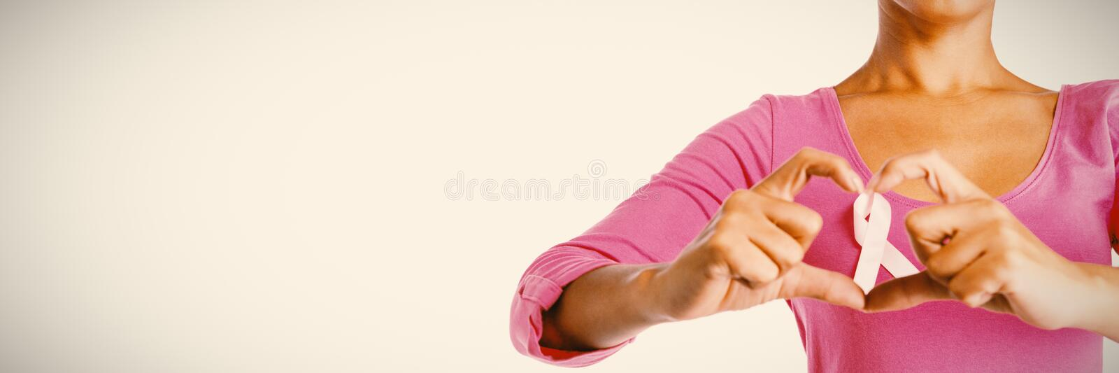Women wearing pink shirt making heart with their fingers around pink ribbon royalty free stock photos