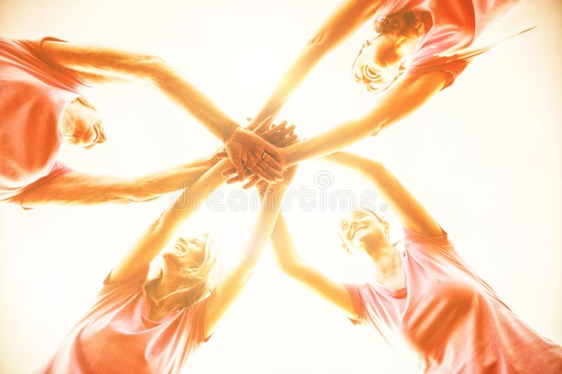 Women wearing pink shirt putting hands together stock photos