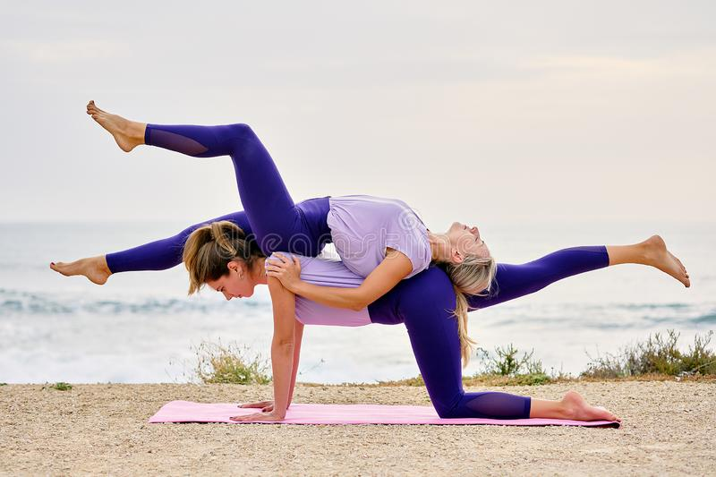 Women doing partner tandem yoga exercise on mat near the sea royalty free stock photo