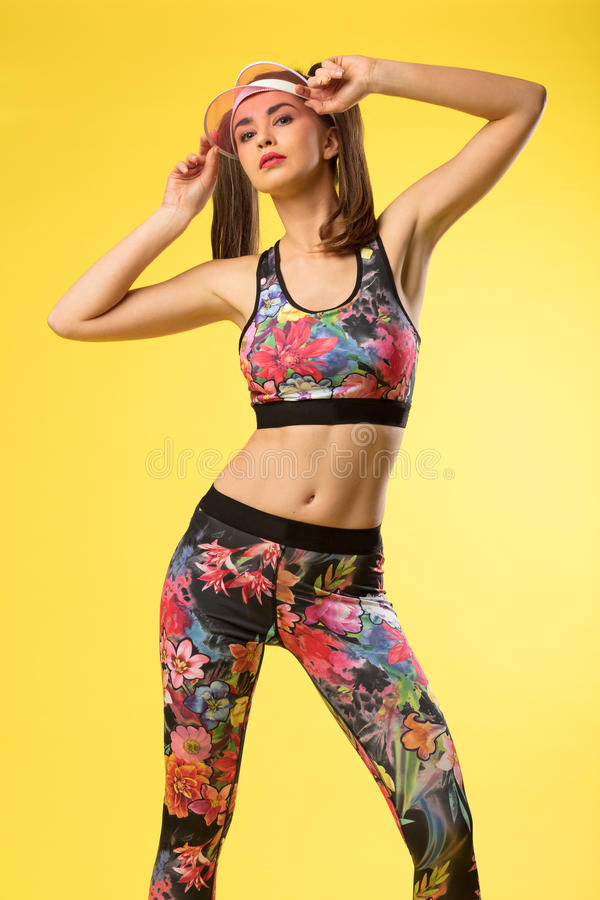 Women wearing sport clothes and cap with her hands up. royalty free stock images