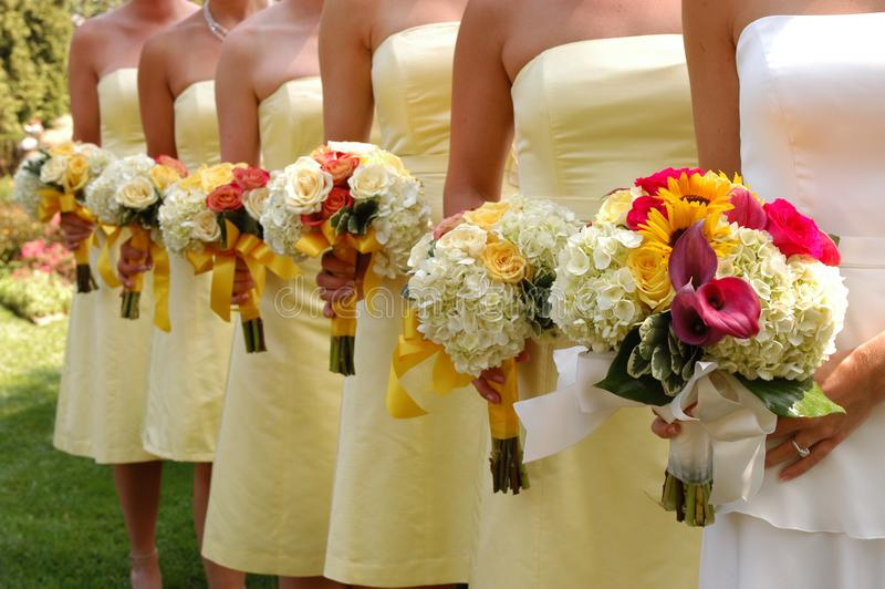 Women Wears White and Yellow Tube Strapless Dresses Holding White, Red, and Yellow Bouquet royalty free stock images