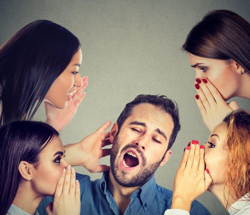 Women whispering a secret latest gossip to a bored sleepy man stock photos