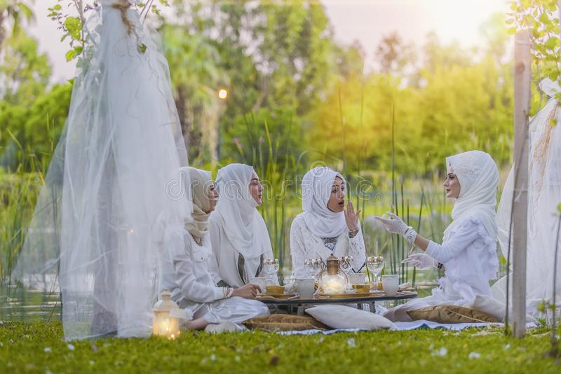 4 Women in White Abaya Wedding Gown Having Picnic Near Trees royalty free stock photography