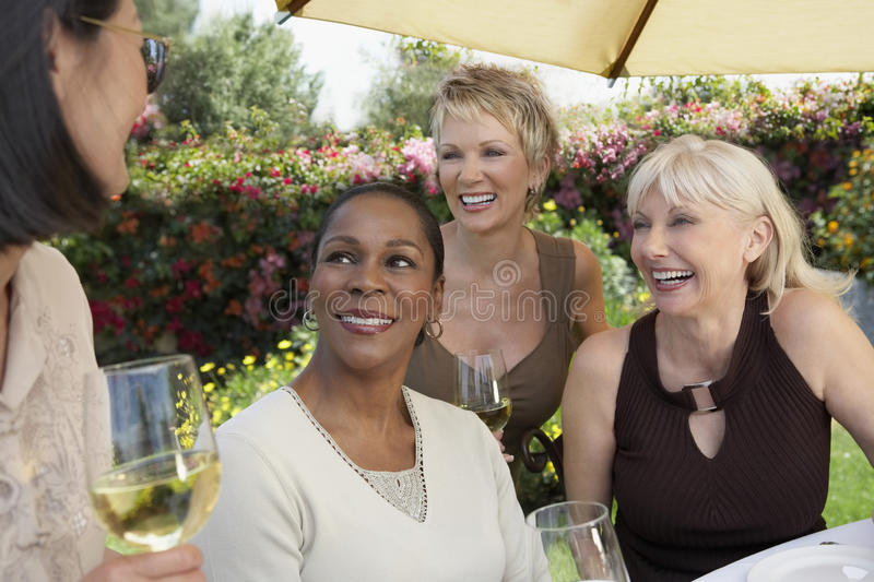 Women With Wine Glasses Chatting At Garden Party. Four cheerful multiethnic middle aged women chatting with wine glasses at the garden party stock photo