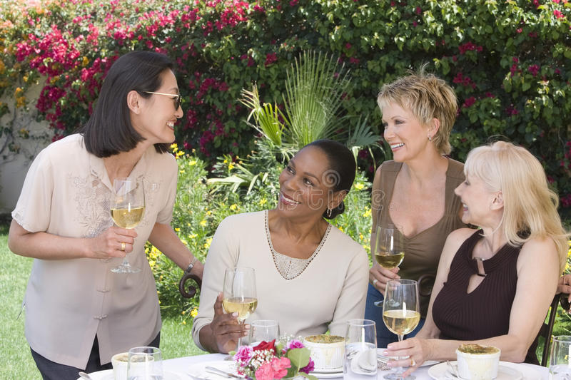 Women With Wine Glasses Chatting At Garden Party. Four happy multiethnic middle aged women chatting with wine glasses at the garden party royalty free stock photography
