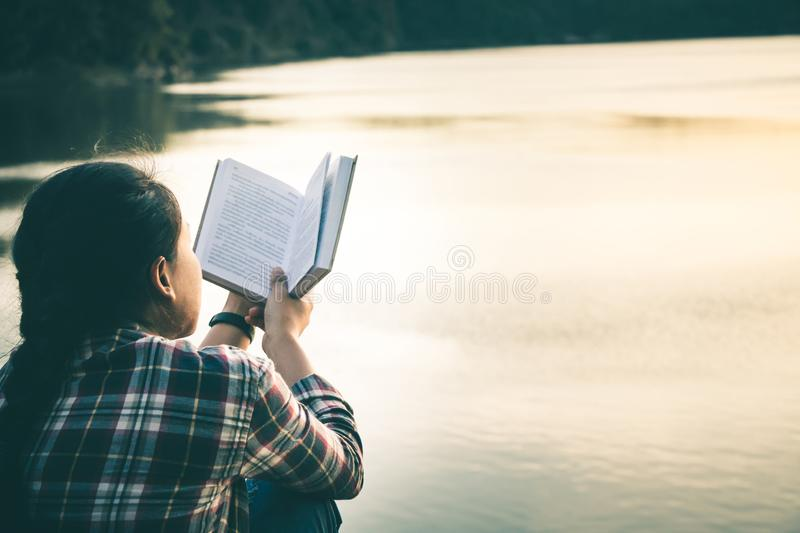 Women in winter sit read favorite book in the holiday. stock image
