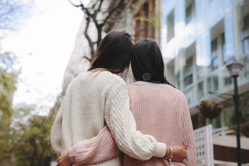 Rear view of two women standing together outdoors stock photos
