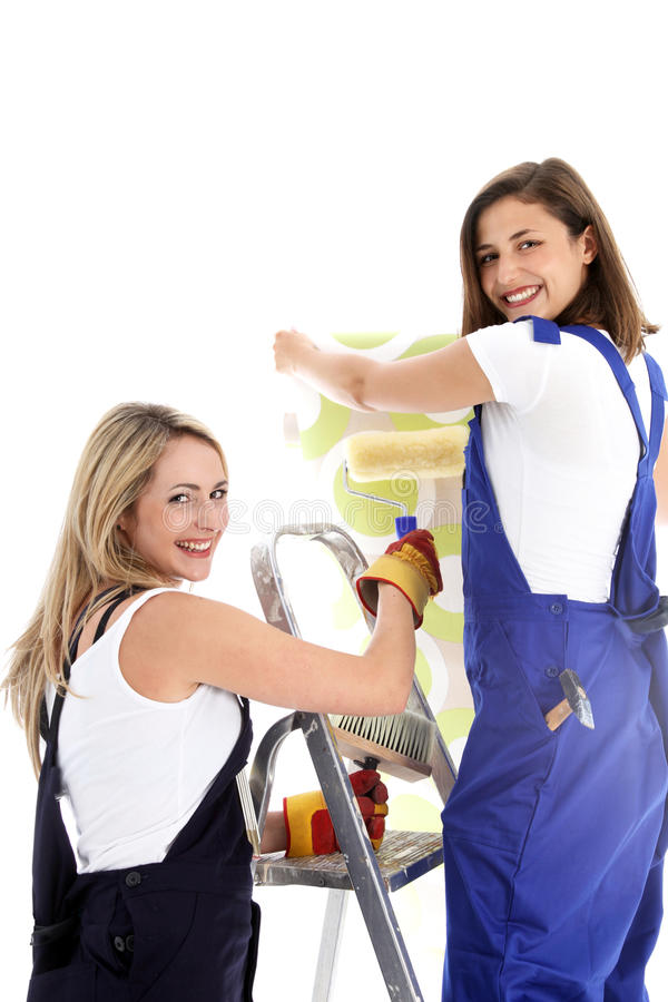 Women at work wallpapering. Two cheerful attractive women at work on a ladder wallpapering and hanging a cut length on a wall isolated on white stock images