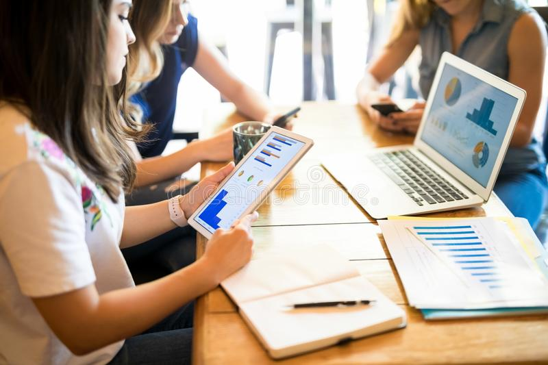Women working on business charts at restaurant. Young women looking at digital tablet with friends sitting by at restaurant table, all working on business charts stock image