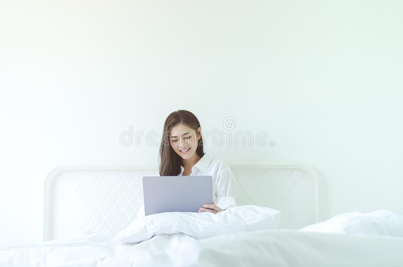 Women are working and happy. Beautiful Asian woman is smiling.Lady work with laptops on the sofa in the room in the morning.She is happy to get a new job royalty free stock photography