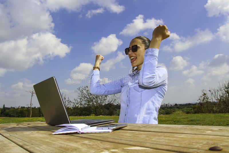 a women with laptop, sitting in the garden and make a great deal, she happy with her arms up stock photo