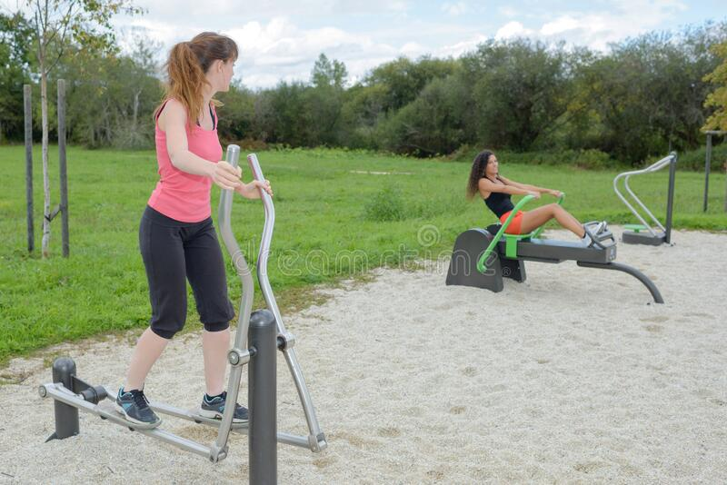 Women working out on equipment in park stock images