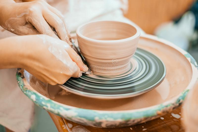 Modeling on a potter`s wheel. Women working on the potter`s wheel. Hands sculpts a cup from clay pot. Workshop on modeling on the potter`s wheel royalty free stock photography