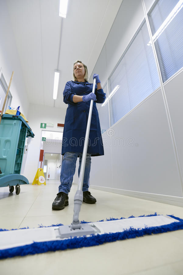 Women at workplace, female cleaner sweeping floor