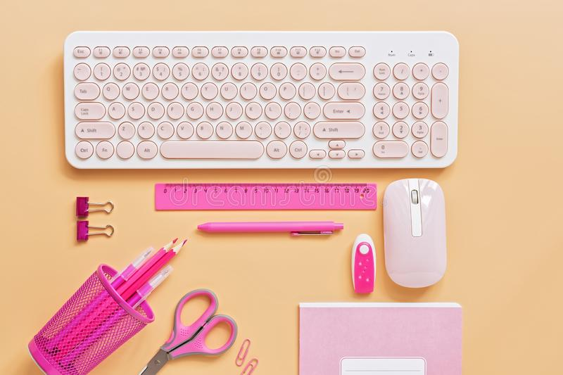 Women workspace with a computer and stationery to pink color on a pastel background. Flat lay, top view office table desk frame. Top view,copy space stock photography