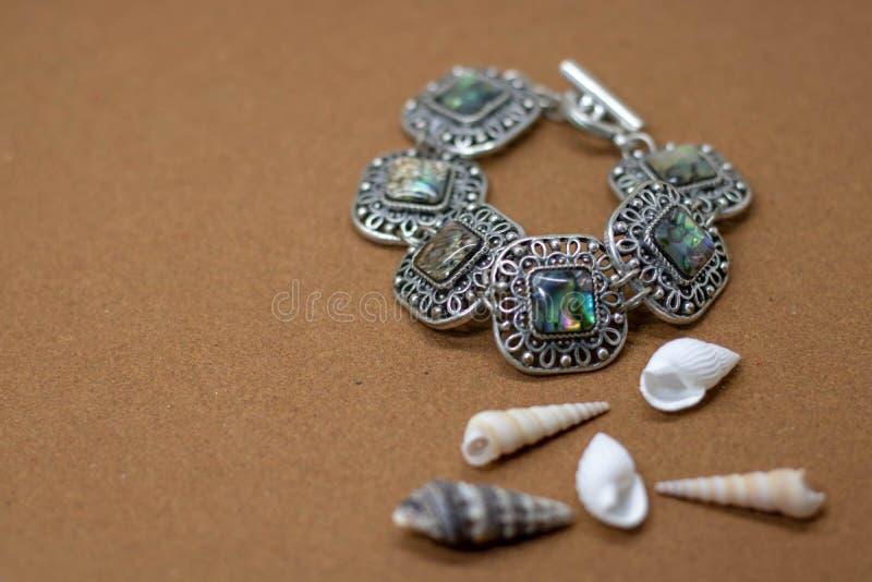 Womens Bracelet aus Perlen, Muscheln, Stern und Steinen auf sandigem Hintergrund Sommerzeitkonzept stockfoto