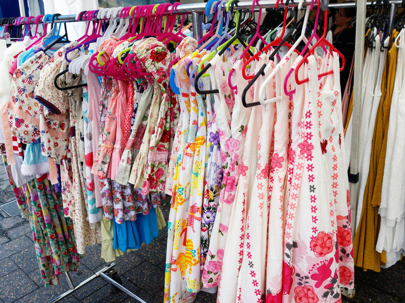 Womens Clothes on Hangers. A number of fashion womens clothes, dresses and skirts, on plastic hangers in clothing street stall royalty free stock images