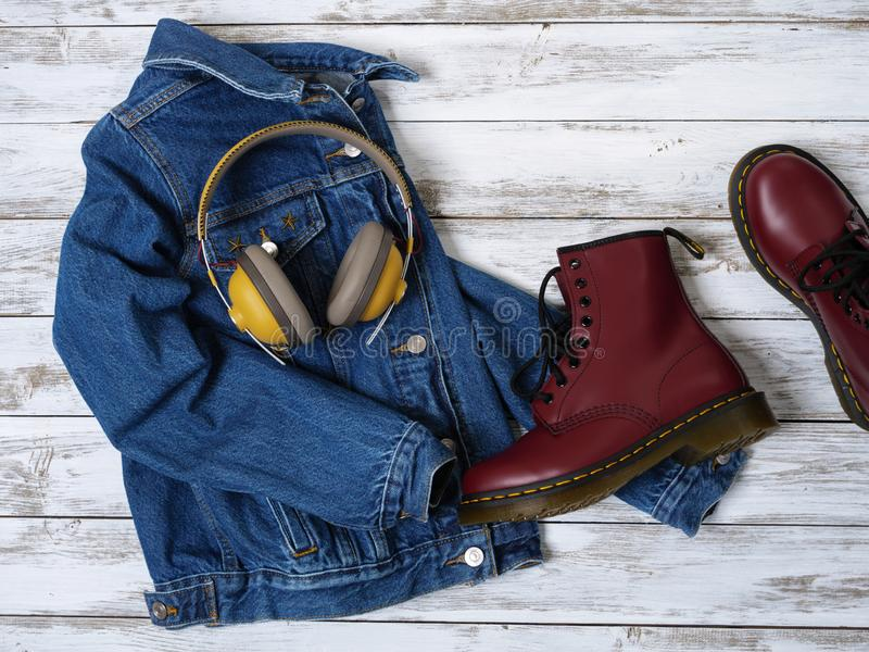Womens clothing, accessories, footwear burgundy boots, yellow wireless headphones, denim jacket. Fashion outfit. Shopping royalty free stock image