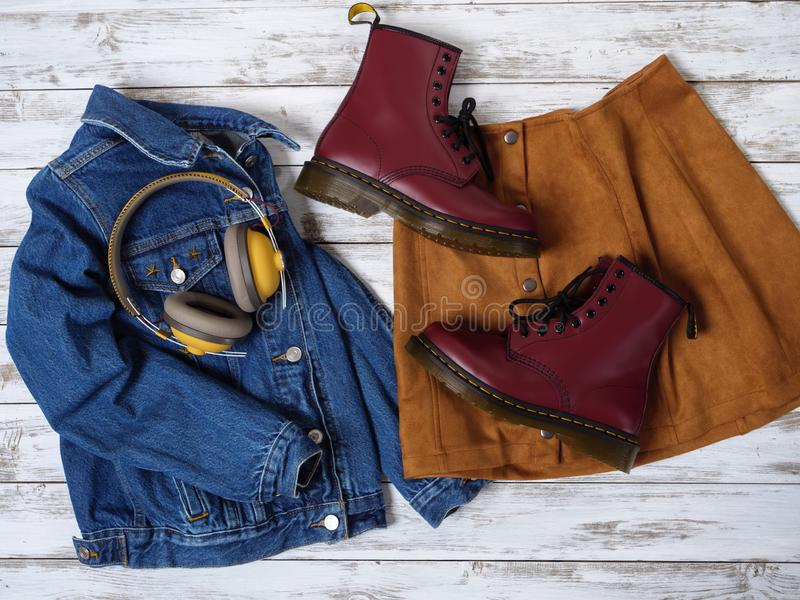 Womens clothing, accessories, footwear burgundy boots, yellow wireless headphones, denim jacket, suede skirt. Fashion outfit. Shopping concept. Flat lay royalty free stock photography