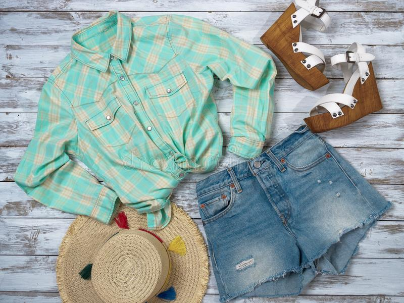 Womens clothing, accessories, shoes plaid shirt, denim shorts, straw hat, wedge sandals. Fashion outfit, spring summer royalty free stock photo