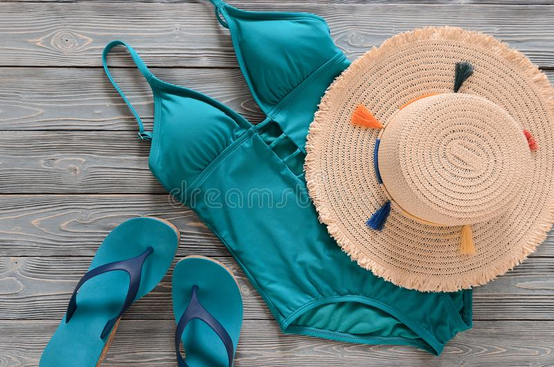 Womens clothing, accessories, shoes straw hat, blue green swims. Uit, flip flops on grey wooden background. Trendy fashion outfit. Shopping, travel, summer stock photography