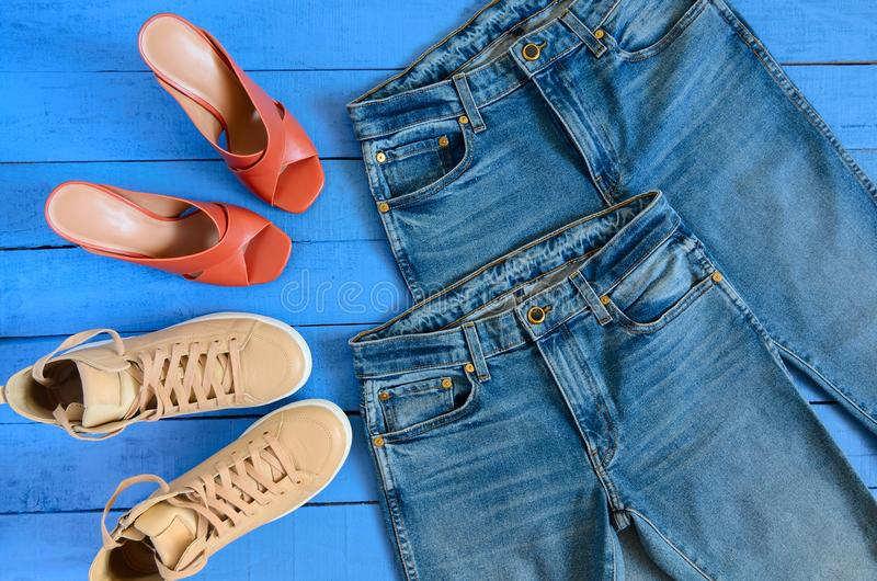 Womens clothing, footwear blue jeans, leather terracotta heel. Shoes, nude sneakers. Fashion outfit. Shopping concept. Flat lay. Trendy, saturated colors royalty free stock image