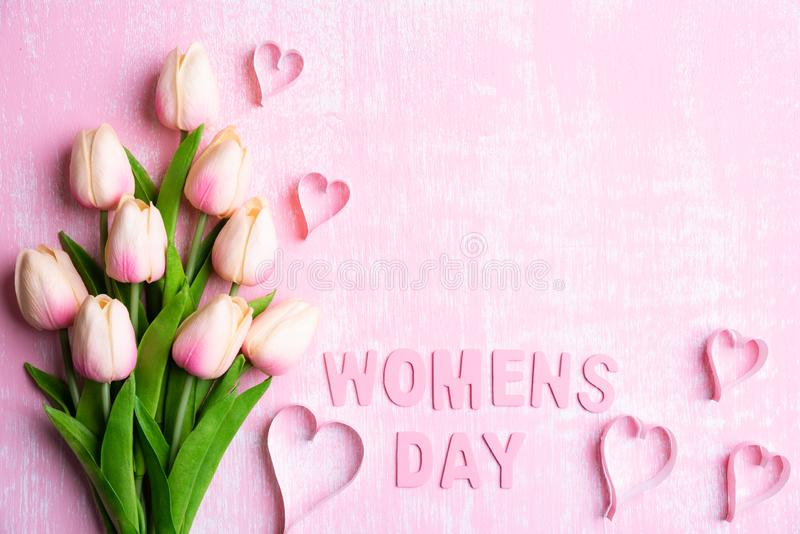 Womens day concept. Pink tulips and paper hearts with Wooden letters forming word Womens day written on pink and white wooden stock photography
