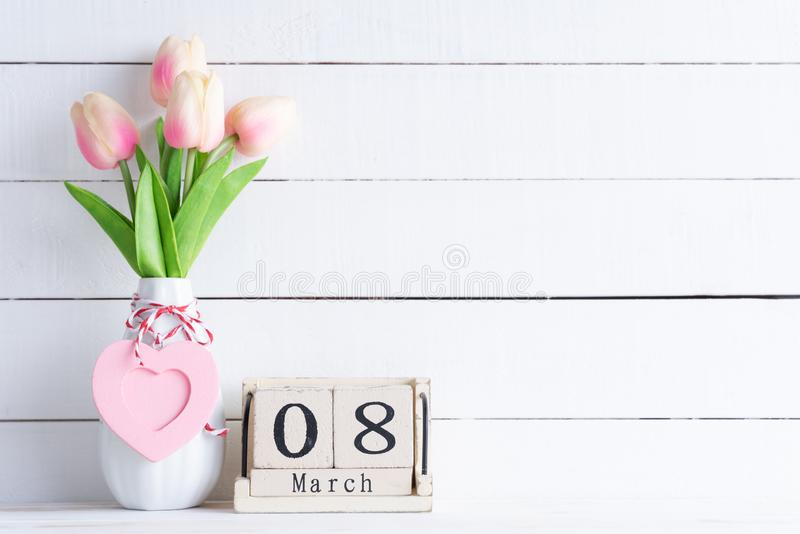 Womens day concept. Pink tulips and red heart with March 8 text on wooden block calendar on white wooden background stock photo