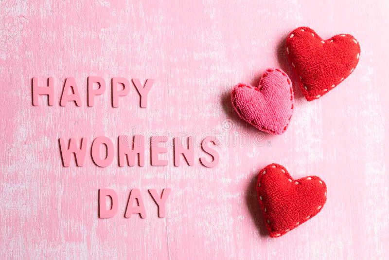 Womens day concept. Red Hearts with Wooden letters forming word Happy Womens day written on pink and white wooden background stock photography