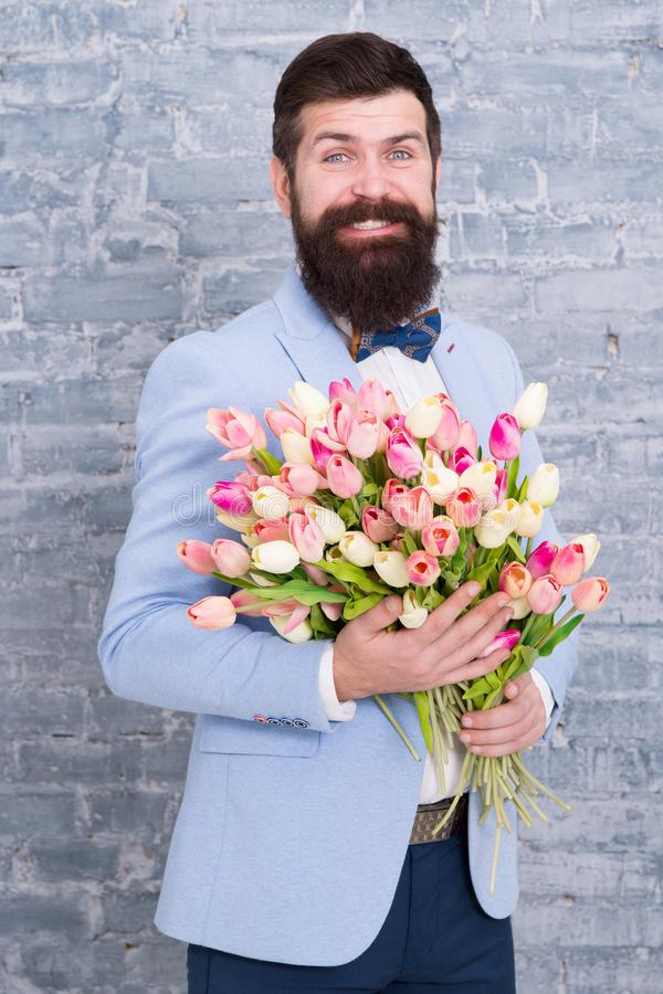 Womens day. Flower for March 8. Love date. international holiday. Bearded man with tulip bouquet. Spring gift. Bearded. Man hipster with spring flowers. spring royalty free stock photo