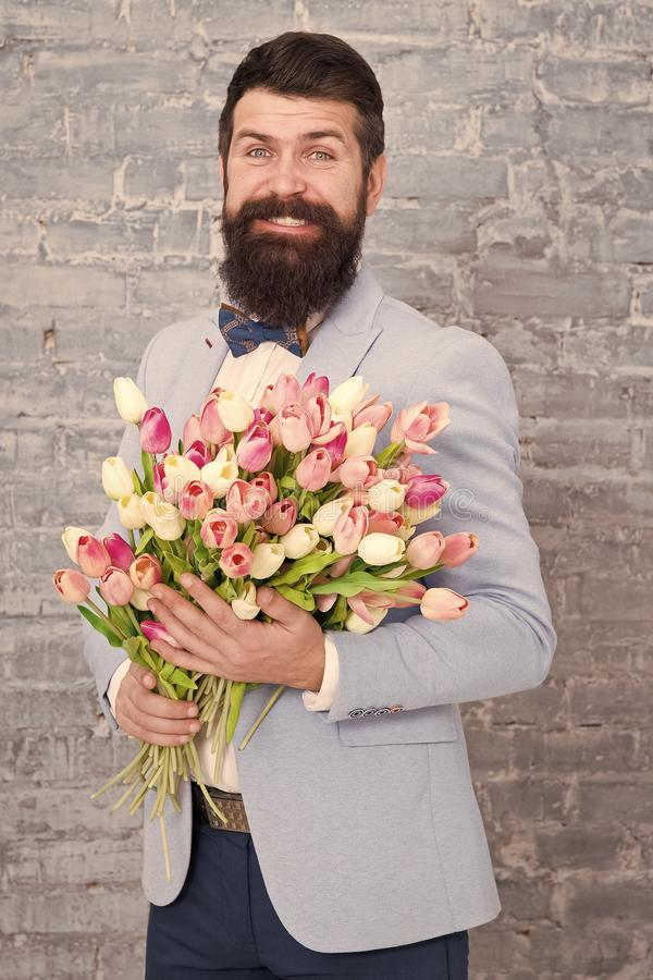 Womens day. Flower for March 8. Love date. international holiday. Bearded man with tulip bouquet. Spring gift. Bearded stock photos