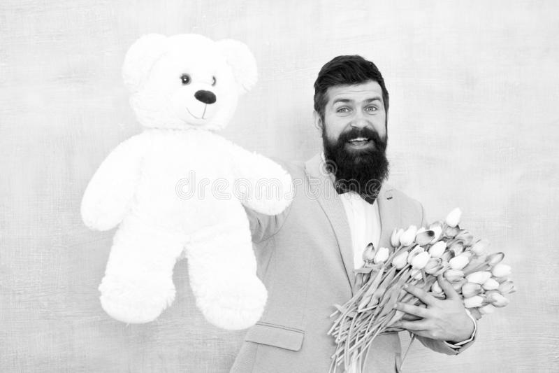 Womens day. Formal businessman with teddy bear toy. spring bouquet. 8 of march. bride groom at wedding party. bearded royalty free stock images