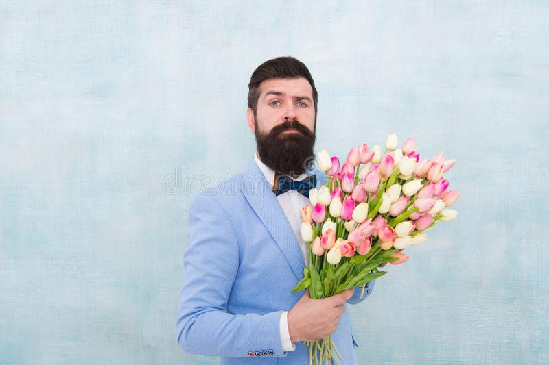 Womens day. Formal mature businessman love date with flowers. Happy Birthday. bride groom at wedding party. spring. Bouquet. 8 of march. bearded man in bow tie stock images