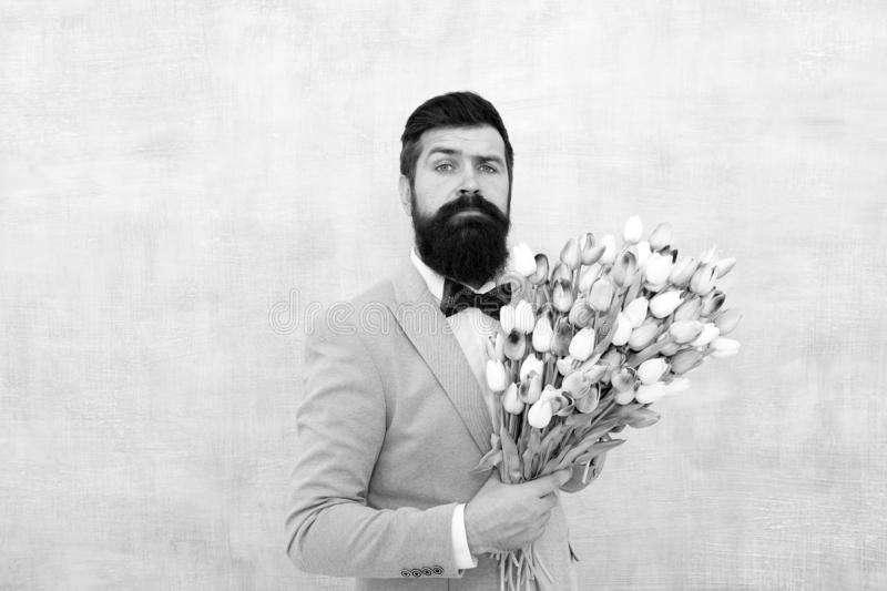 Womens day. Formal mature businessman love date with flowers. Happy Birthday. bride groom at wedding party. spring. Bouquet. 8 of march. bearded man in bow tie royalty free stock photography