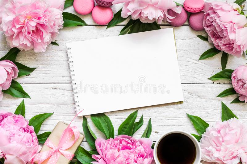 Womens day or wedding background. paper blank, peony flowers, macaroons, gift box on white wooden table royalty free stock photo