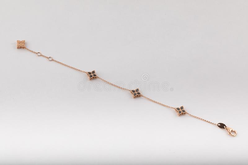 Womens gold bracelet with black diamonds in the shape of flowers isolated on white background. royalty free stock photo