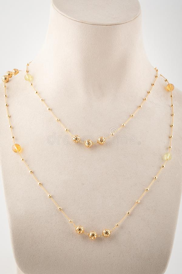 Womens gold double chain with beads, golden stones on white mannequin royalty free stock photo
