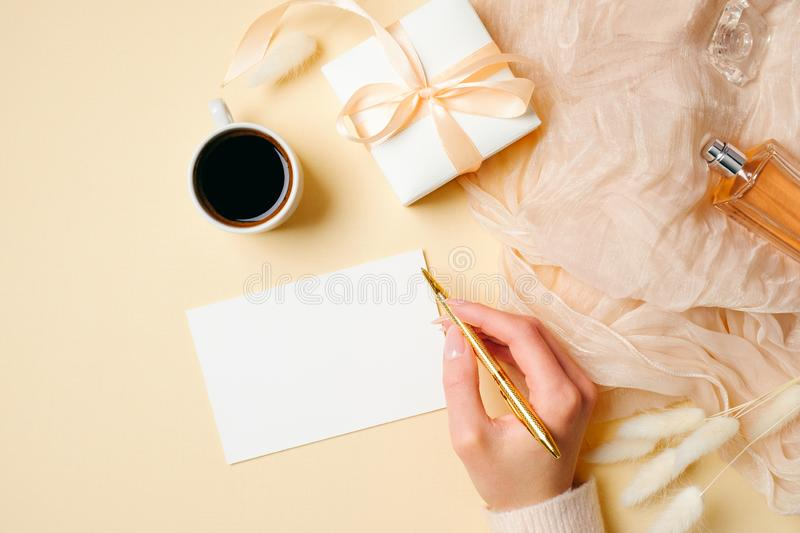 Womens hand holding golden pen and write message on blank paper card on beige feminine background with stylish accessories, royalty free stock images