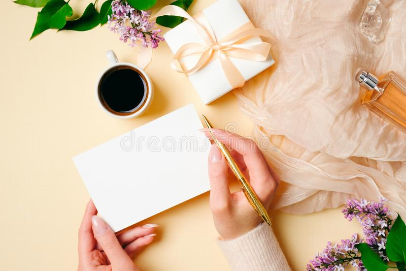 Womens hand holding golden pen and write message on blank paper card on beige feminine background with stylish accessories, royalty free stock photography