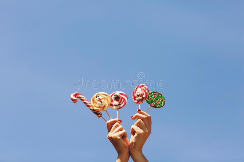 Womens hands holding colored Christmas candies on the blue sky background. Space for text. Christmas concept royalty free stock image