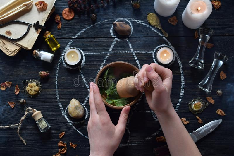Womens hands make love potion on pentagram circle with candles, stones and old books on witch table. Occult, esoteric or. The womens hands make love potion on royalty free stock image