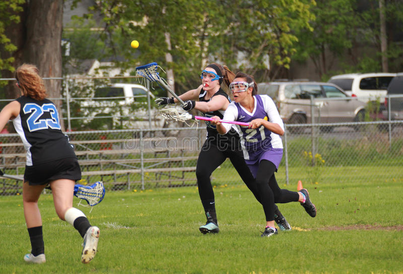 Womens Lacrosse. The ball was passed by the Waukesha goalie. Both teams are in pursuit. This is a Girls Varsity Lacrosse game on May 18, 2011 in Waukesha, WI royalty free stock photography