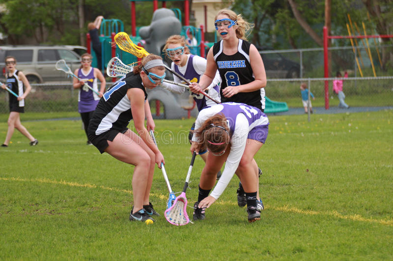 Womens Lacrosse. Both mid players trying to scoop up a loose ball. This is a Girls Varsity Lacrosse game on May 18, 2011 in Waukesha, WI, between Waukesha West royalty free stock images