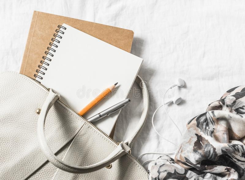 Womens leather handbag, clean blank notepad, pen and scarf on a light background, top view. Free space. For text royalty free stock photo