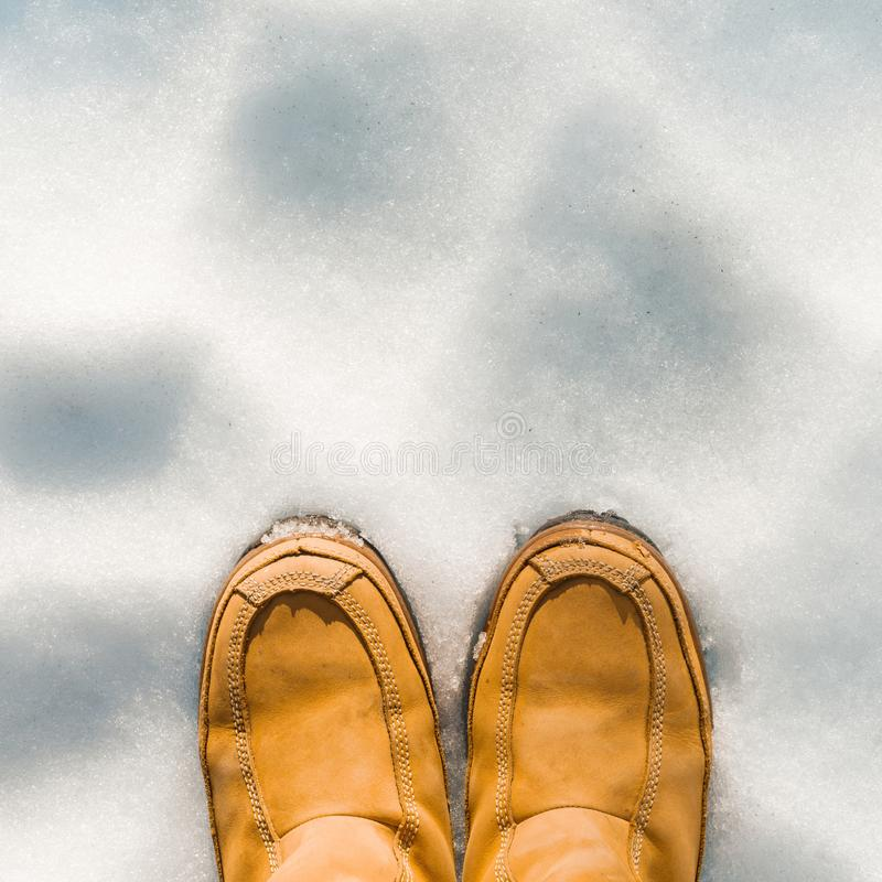 Womens legs in boots in the snow, winter is coming, hello winters, copy space at the top, top view close up royalty free stock images