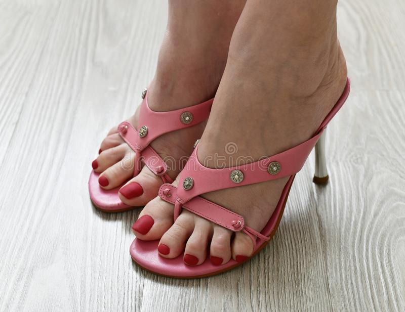 Womens legs in summer pink heeled sandals royalty free stock images