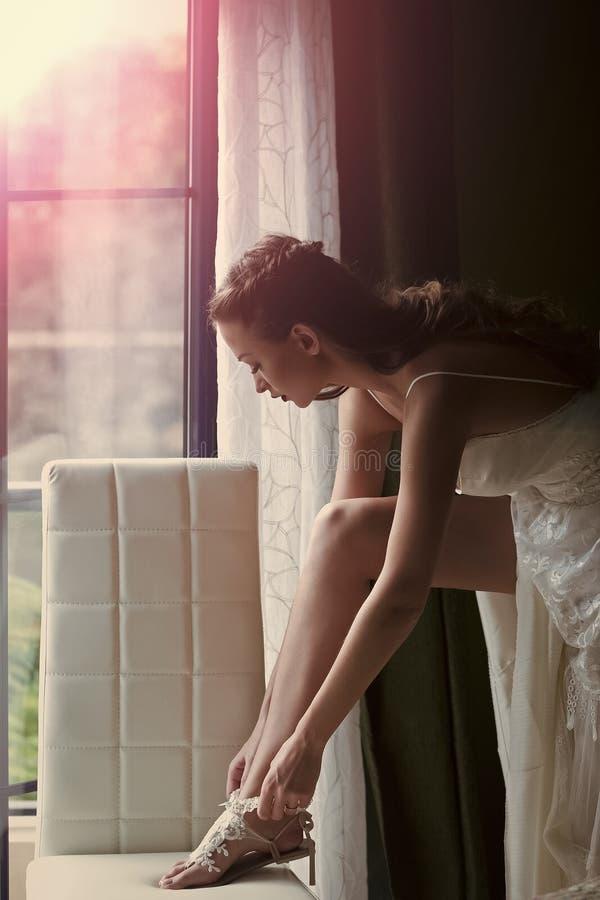 Womens secrets. Pretty bride wears lace garter on sexi leg. Womens secrets. beautiful bride, woman in white dress wears lace garter on sexi leg on wedding day on stock photography