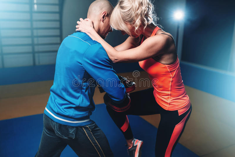 Womens self defense workout with instructor. Womens self defense workout with personal instructor, fighting training in gym, martial art stock photos