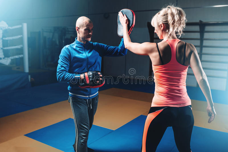 Womens self-defense workout with personal trainer. Fighting training in gym, martial art stock photo