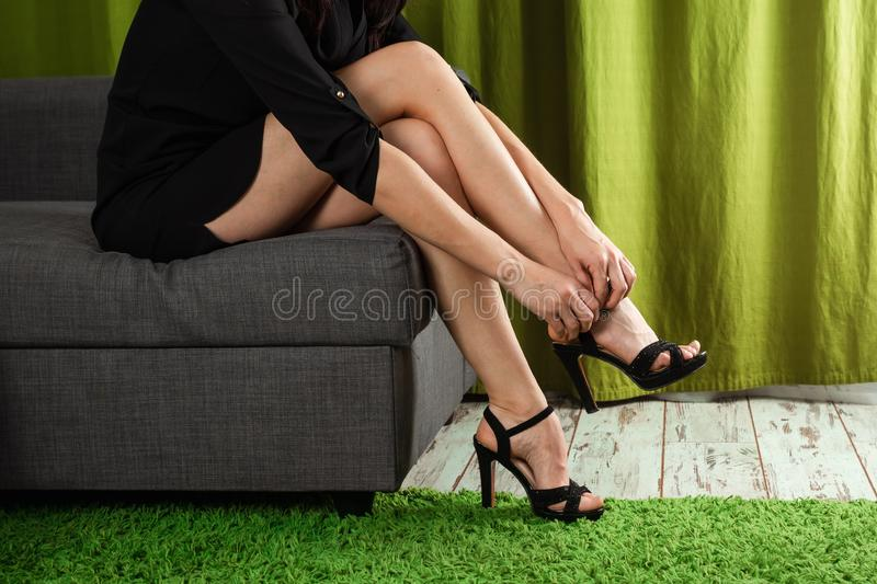 Womens sexy legs. Woman buttons her high heel shoes. Beautiful woman legs wearing dress with high heel shoes. Concept shoes, women royalty free stock photo